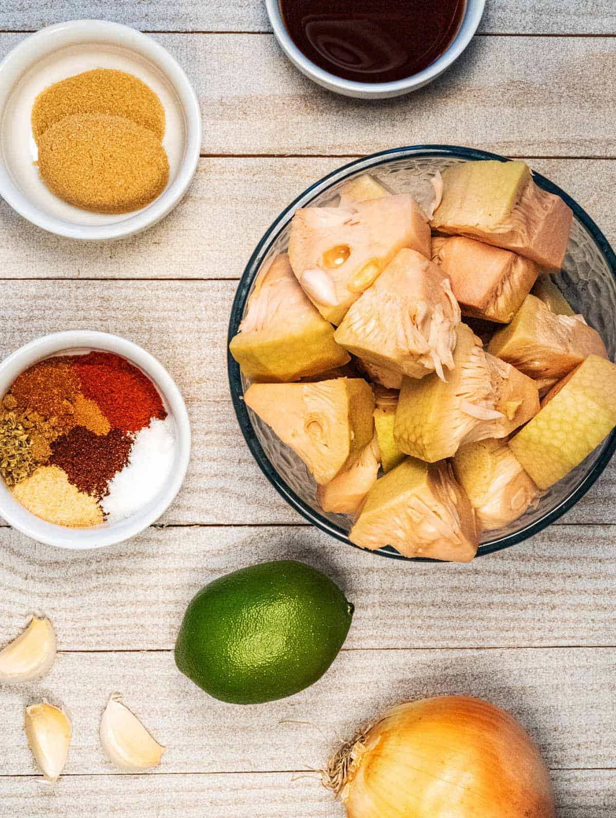 Jackfruit, lime, spices, garlic, onion, and soy sauce in dishes on a white wood table.