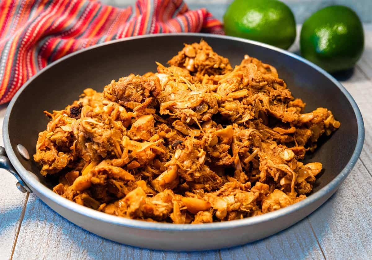 A skillet of jackfruit carnitas on a white wood table with a red towel and limes.