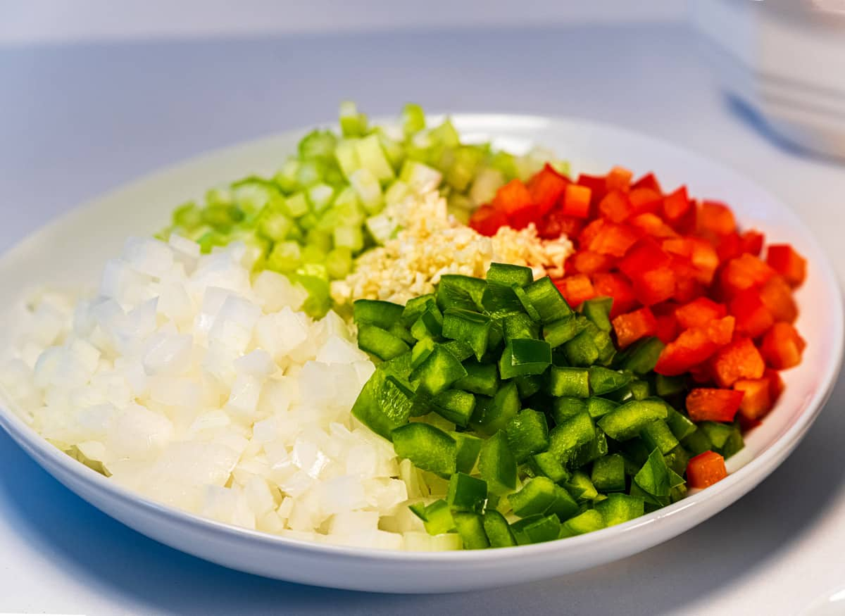 Diced onion, bell pepper, celery, and garlic on a plate.