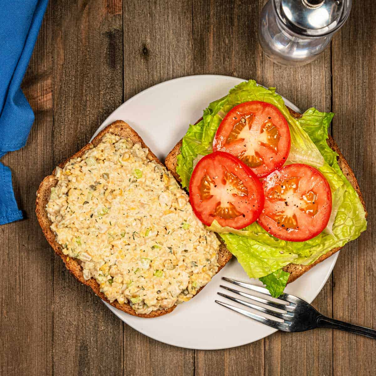 Chickpea tuna salad sandwich open faced on a plate.