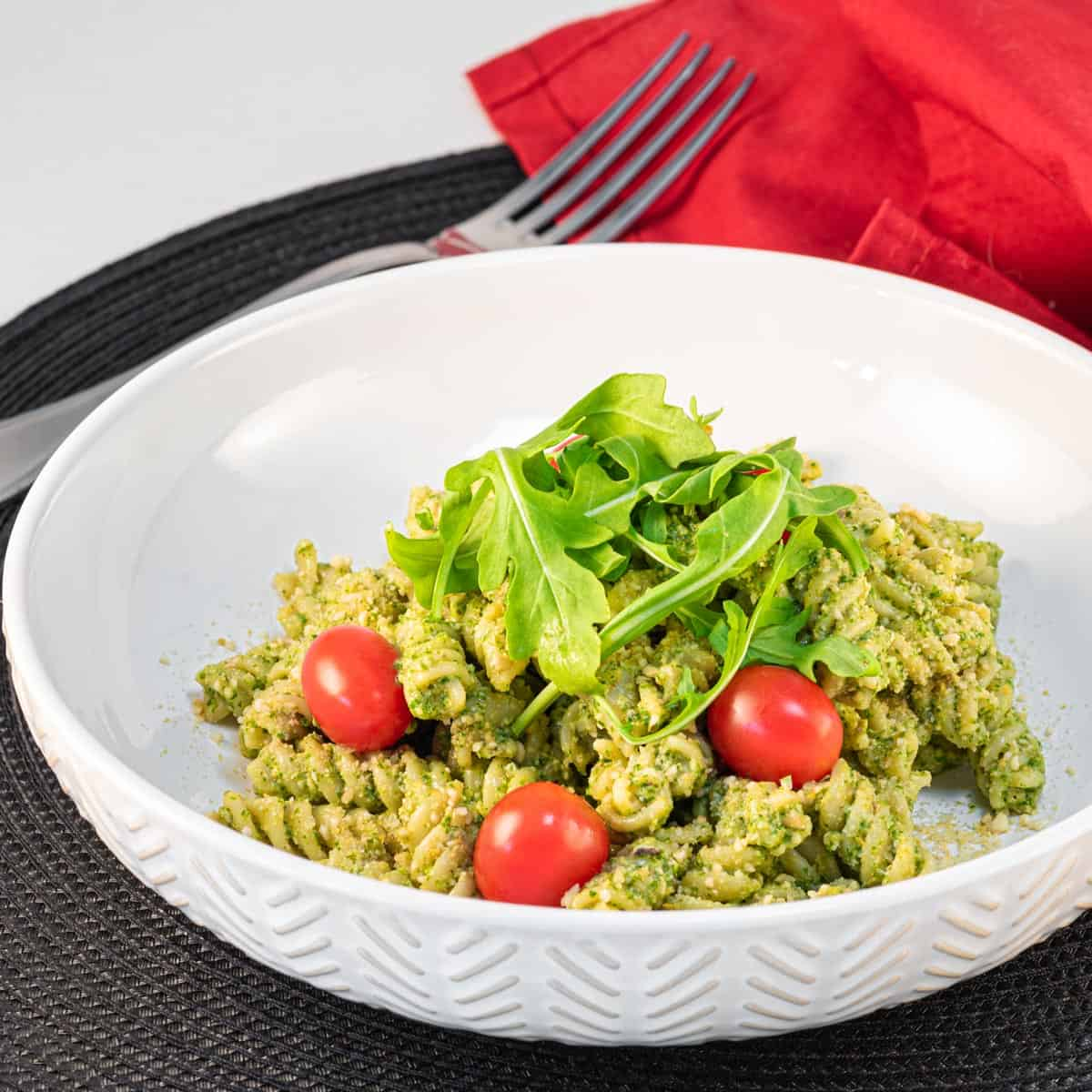 Bowl of vegan pesto pasta topped with arugula and tomatoes.