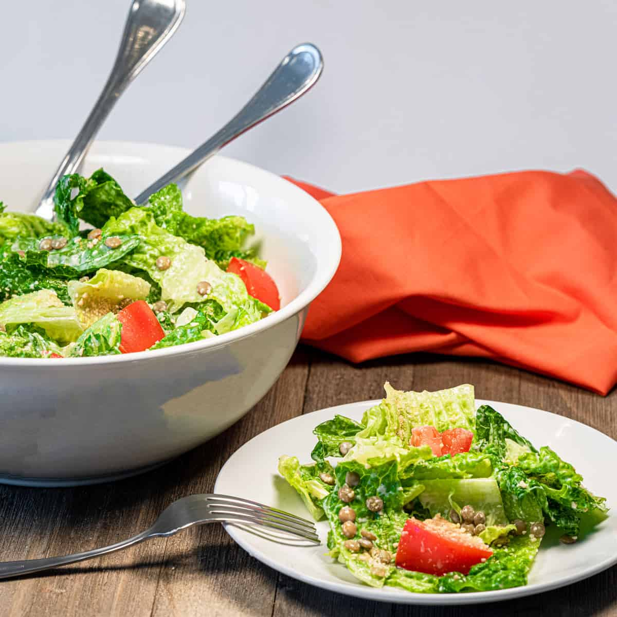 A plate of vegan caesar salad with a bowl of it in the background.